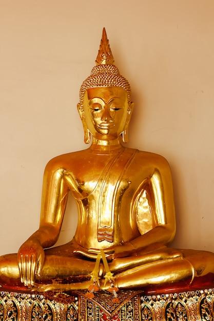 Schöner goldener buddha auf dem sockel einige weiße wände Premium Fotos
