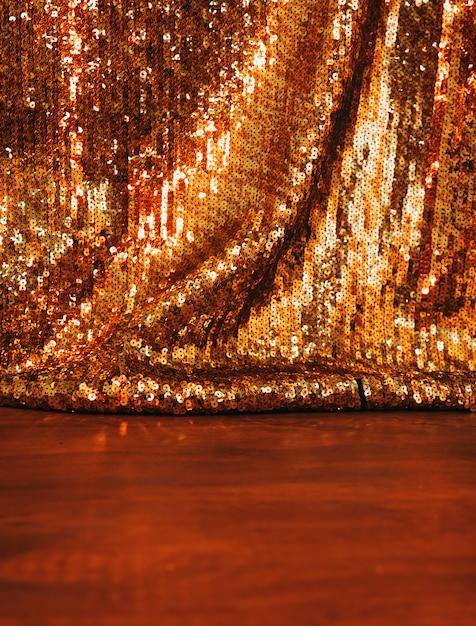 Schöner goldener funkelnpaillettehintergrund auf holzoberfläche Kostenlose Fotos