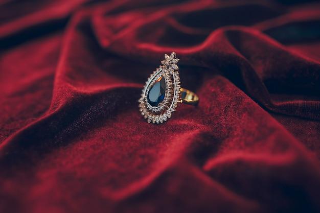 Schöner goldener schmuck mit jem auf rotem samthintergrund Premium Fotos
