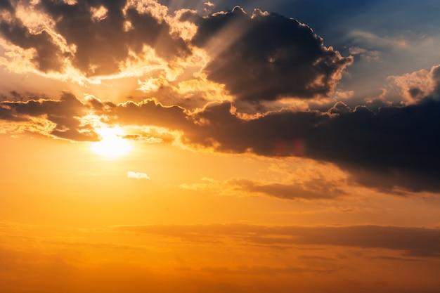 Schöner goldener sonnenuntergang im himmel mit sonne strahlt durch die wolken aus Premium Fotos