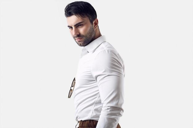 Schöner grober gebräunter geschäftsmann in einem weißen hemd und in einer sonnenbrille Premium Fotos