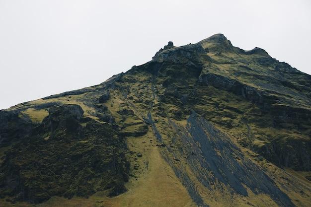 Schöner grüner steiler hügel mit einem klaren weißen himmel im hintergrund Kostenlose Fotos