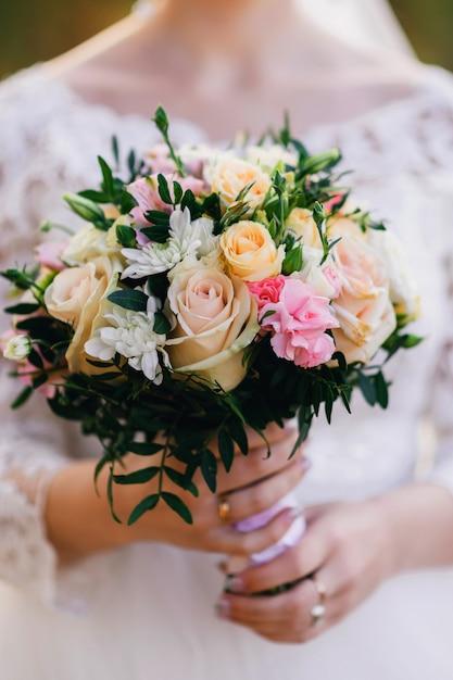 Schöner hochzeitsblumenstrauß mit gelben rosen, weißen chrysanthemen und alstroemeria in den händen der braut Premium Fotos