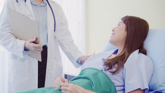 Schöner intelligenter asiatischer doktor und patient, die etwas mit klemmbrett bespricht und erklärt Kostenlose Fotos