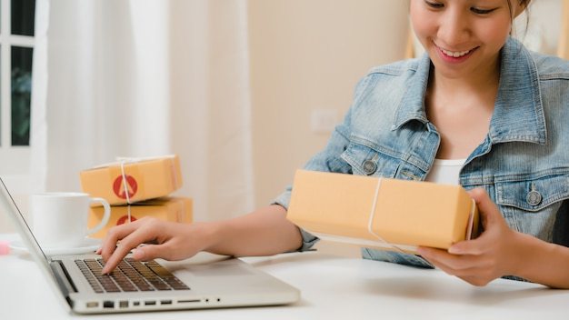 Schöner intelligenter asiatischer jungunternehmergeschäftsfrauinhaber von kmu, das produkt auf lager online überprüft und zum computer speichert, der zu hause arbeitet. Kostenlose Fotos