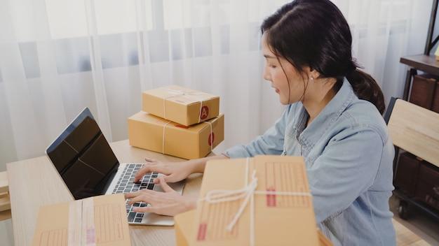 Schöner intelligenter asiatischer jungunternehmergeschäftsfrauinhaber von kmu, das produkt online überprüft Kostenlose Fotos