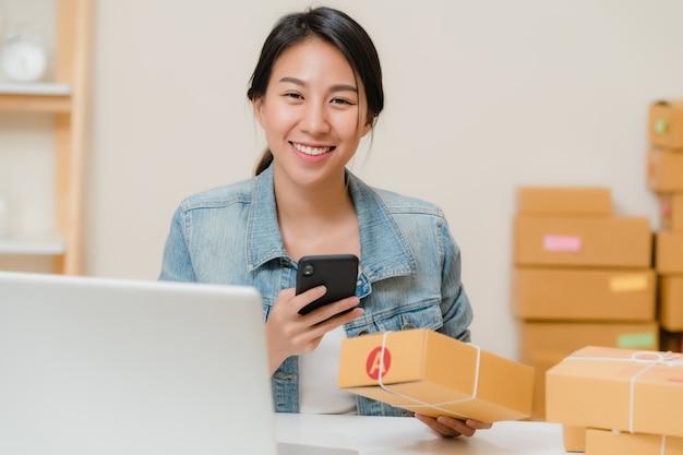 Schöner intelligenter asiatischer jungunternehmergeschäftsfrauinhaber von kmu, der scan-qr-code des auf lager zu hause arbeitenden codes überprüft. Kostenlose Fotos