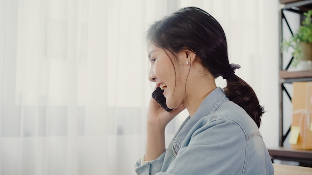 Schöner intelligenter asiatischer jungunternehmergeschäftsfrauinhaber von kmu online unter verwendung des smartphoneanrufs Kostenlose Fotos