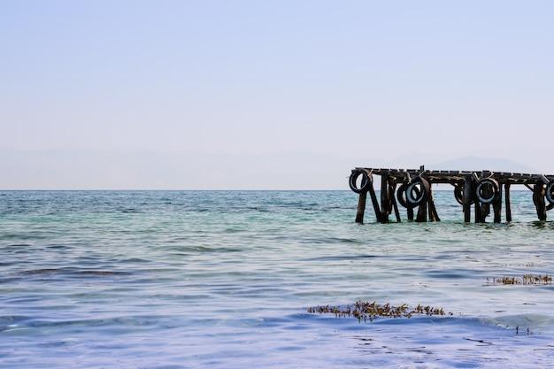 Schöner jachthafen auf naturufer des seehintergrundes. alter hölzerner pier auf seeküstenlinie, klarer himmel. Premium Fotos