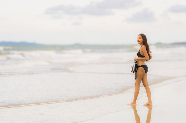 Schöner junger asiatischer frauenabnutzungsbikini des porträts auf dem strandseeozean Kostenlose Fotos