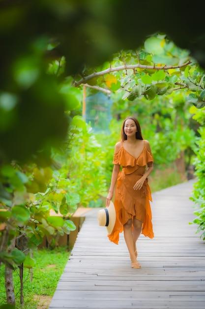 Schöner junger asiatischer frauenweg des porträts auf wegweg im garten Kostenlose Fotos