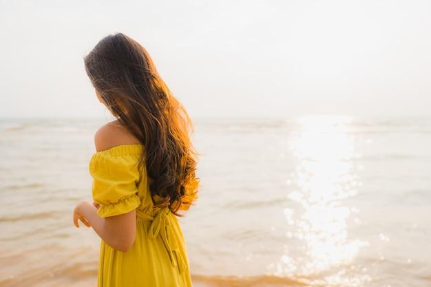 Schöner junger asiatischer frauenweg des portraits auf dem strand- und seeozean mit dem glücklichen lächeln entspannen sich Kostenlose Fotos