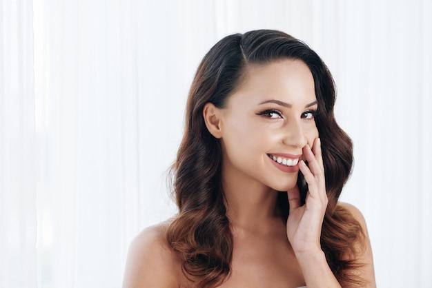 Schöner junger brunette mit den bloßen schultern, die backe und das lächeln berühren Kostenlose Fotos