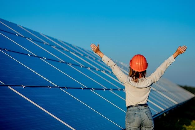 Schöner junger ingenieur, der nahe sonnenkollektoren im freien steht, green energy concept. Premium Fotos