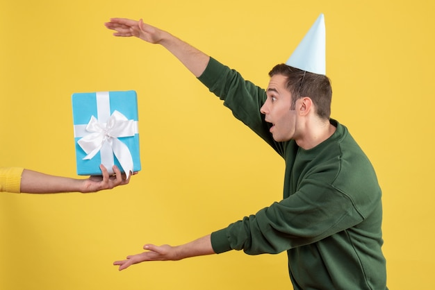 Schöner junger mann der vorderansicht, der geschenk von menschlicher hand auf gelb nimmt Kostenlose Fotos