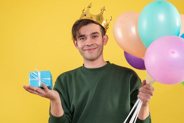 Schöner junger mann der vorderansicht mit der krone, die luftballons und blaue geschenkbox auf gelb hält Kostenlose Fotos
