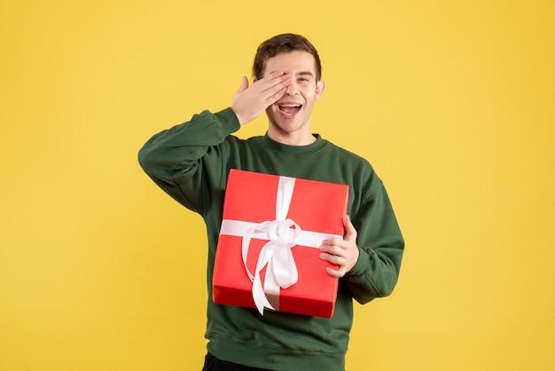 Schöner junger mann der vorderansicht mit grünem pullover, der auf gelb steht Kostenlose Fotos