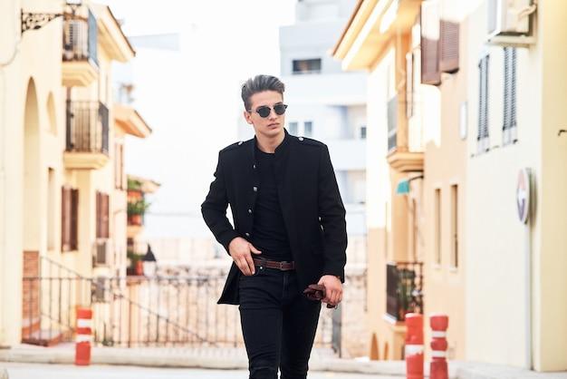 Schöner junger mann in schwarz Premium Fotos
