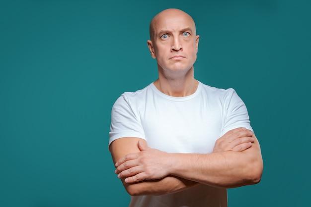 Schöner kahler ernster mann im weißen t-shirt Premium Fotos