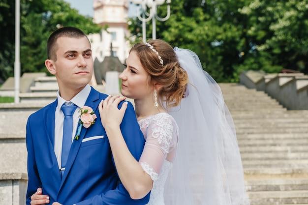 Schöner kerl und mädchen, braut in einem weißen hochzeitskleid, bräutigam in einer klassischen blauen klage gegen einen naturhintergrund. hochzeit, familiengründung. Premium Fotos
