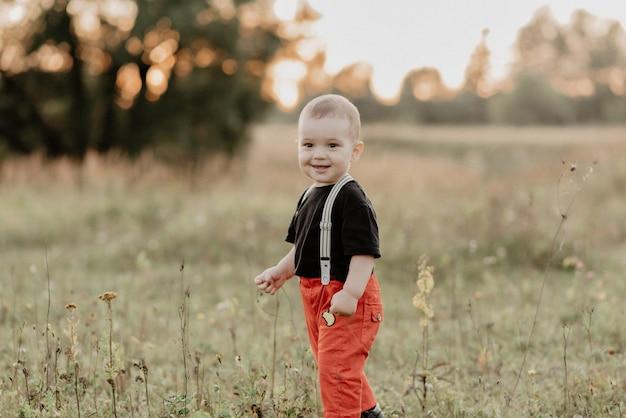 Schöner kleiner junge, der das gehen auf gras lächelt Premium Fotos