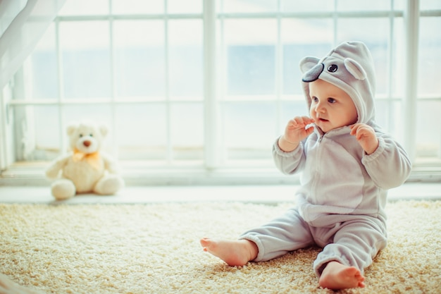 Schöner kleiner junge sitzt am fenster Kostenlose Fotos