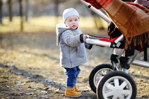 Schöner kleinkindjunge, der mit seinem spaziergänger draußen geht am warmen frühlingstag spielt Premium Fotos