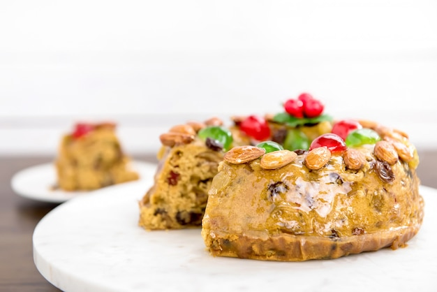 Schöner köstlicher selbst gemachter weihnachtsfruchtkuchen auf weißer servierplatte Premium Fotos