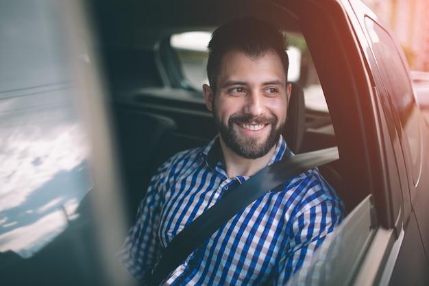 Schöner lächelnder mann beim sitzen auf rücksitz im auto Premium Fotos