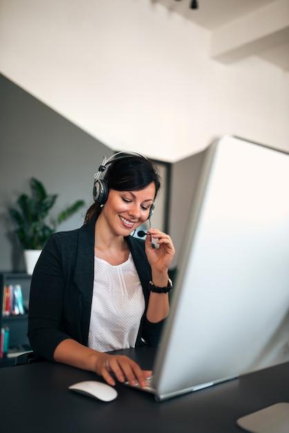 Schöner lächelnder weiblicher betreiber, der auf dem kopfhörer mit kunden spricht. Premium Fotos