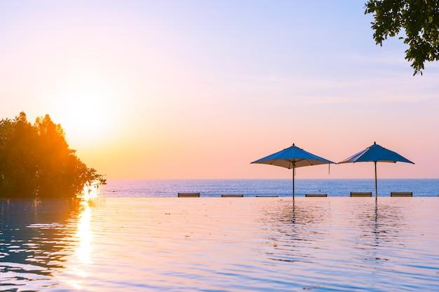 Schöner landschaftsaußenpool mit regenschirm und klappstuhl im hotelerholungsort für entspannen sich tra Kostenlose Fotos