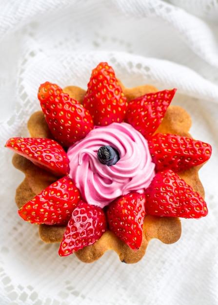 Schöner leckerer cupcake hautnah mit erdbeeren, geißblatt und rosa sahne Premium Fotos