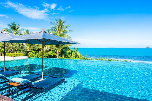 Schöner luxusaußenpool im hotelerholungsort mit seeozean um kokosnusspalme und weiße wolke auf blauem himmel Kostenlose Fotos