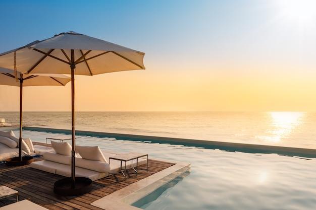 Schöner luxuspool auf seeansicht und regenschirm und stuhl im hotel nehmen zuflucht Premium Fotos