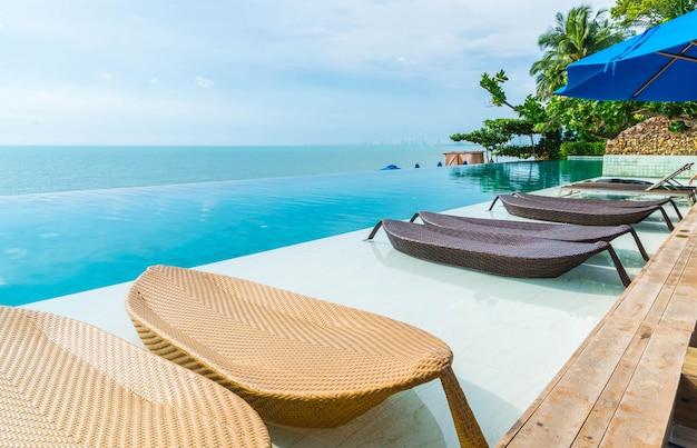 Schöner luxusregenschirm und -stuhl um swimmingpool im hotel und im erholungsort Premium Fotos
