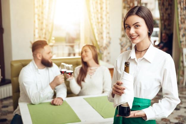 Schöner mädchenkellner hält offene flasche wein Premium Fotos