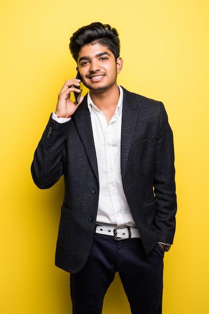 Schöner mann des asiatischen geschäftsmannes wi sprechen auf smartphone auf gelber wand Kostenlose Fotos