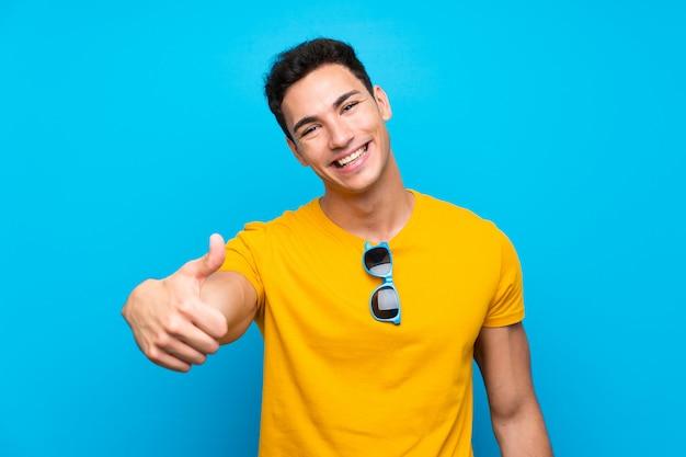 Schöner mann über blau mit daumen hoch, weil etwas gutes passiert ist Premium Fotos