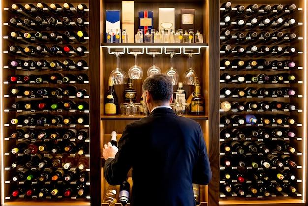 Schöner mann von mittlerem alter wählt eine flasche wein Premium Fotos