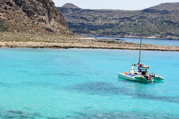 Schöner meerblick mit weißer segeljacht im blauen meer. die segel gesenkt, ruhig. Premium Fotos