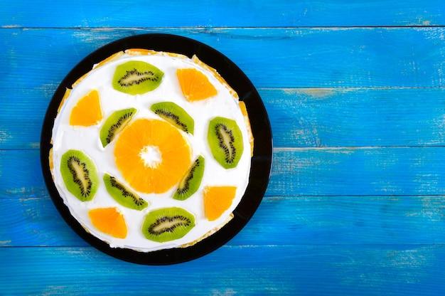 Schöner obstkuchen auf einem blauen hölzernen hintergrund. festlicher kuchen mit orangen, kiwi. draufsicht. alles gute zum geburtstag. Premium Fotos