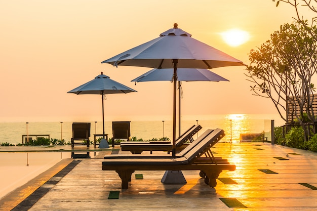 Schöner regenschirm und stuhl rund um den pool in hotel und resort Kostenlose Fotos