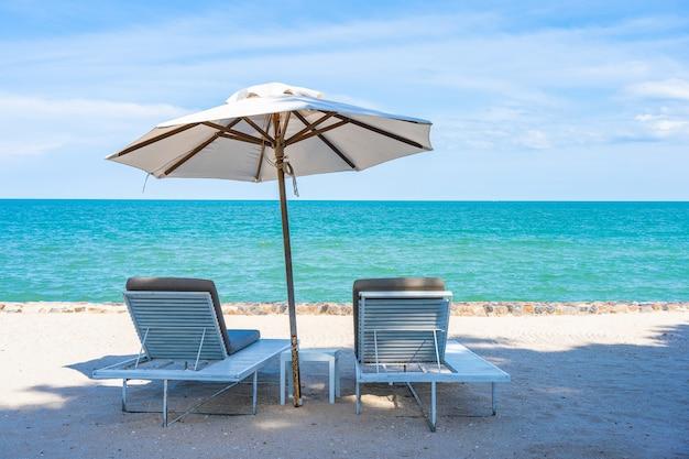 Schöner regenschirm und stuhl um strandseeozean mit blauem himmel für reise Kostenlose Fotos