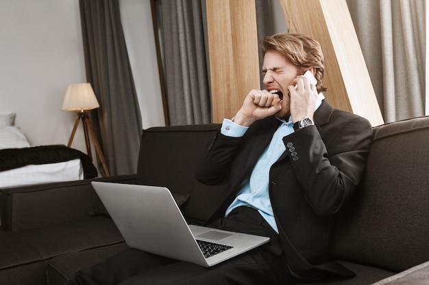 Schöner reifer bärtiger mann im anzug, der im schlafzimmer mit laptop sitzt und sich durch telefonat mit chef über arbeit am späten abend langweilt Kostenlose Fotos