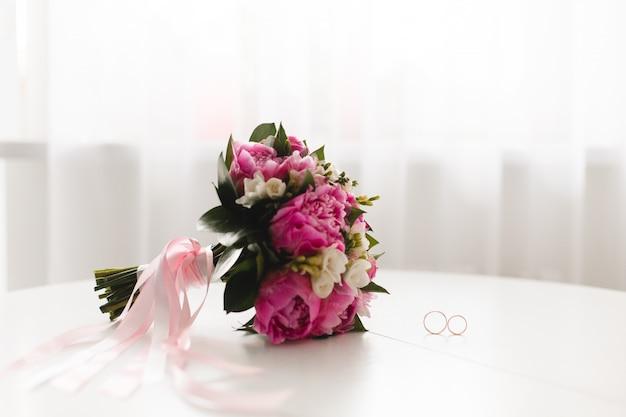 Schöner rosa pfingstrosenblumenstrauß und -eheringe liegen auf einer weißen tabelle. Premium Fotos