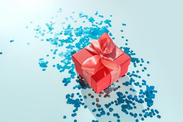 Schöner roter geschenkkarton mit glänzendem satin-korallenband auf türkis Premium Fotos