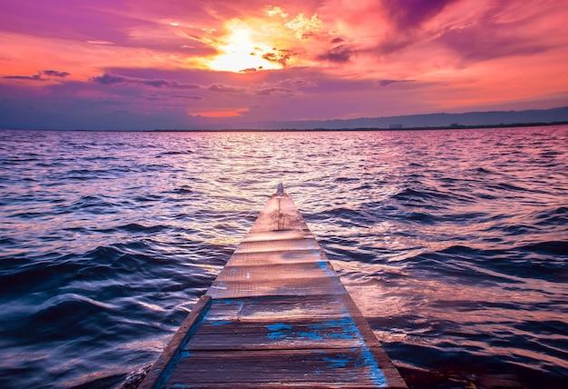 Schöner schuss der nase eines kleinen bootes, das im meer mit erstaunlichen wolken am roten himmel segelt Kostenlose Fotos