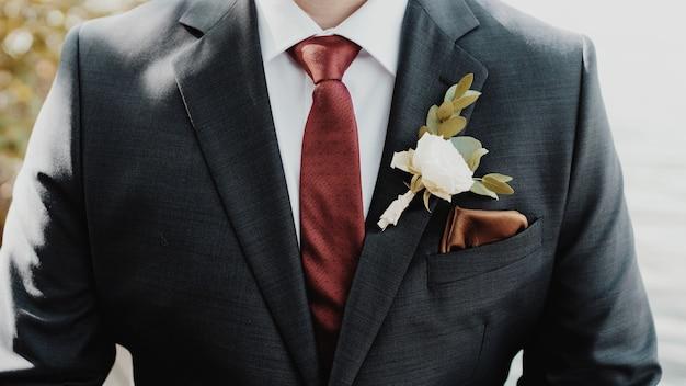 Schöner schuss des bräutigams mit einer weißen blume auf einem anzug Kostenlose Fotos