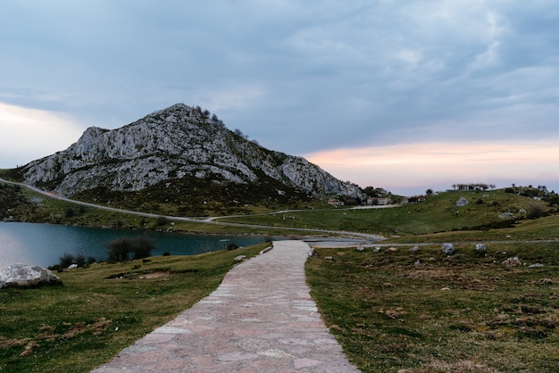 Schöner schuss des felsigen berges nahe dem see an einem bewölkten tag Kostenlose Fotos