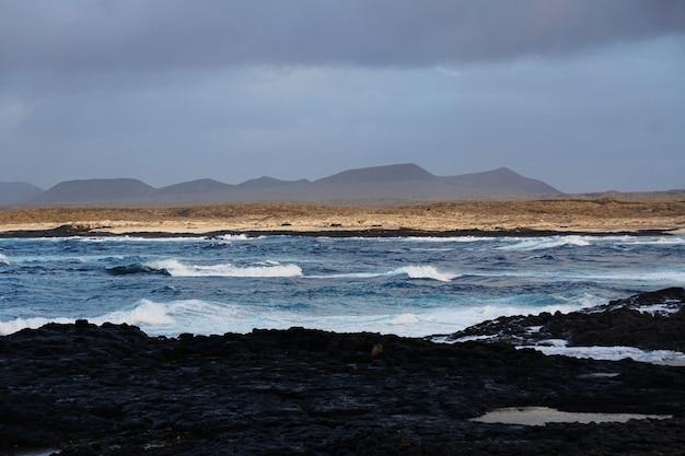 Schöner schuss des felsigen strandes und der berge in fuerteventura, spanien Kostenlose Fotos